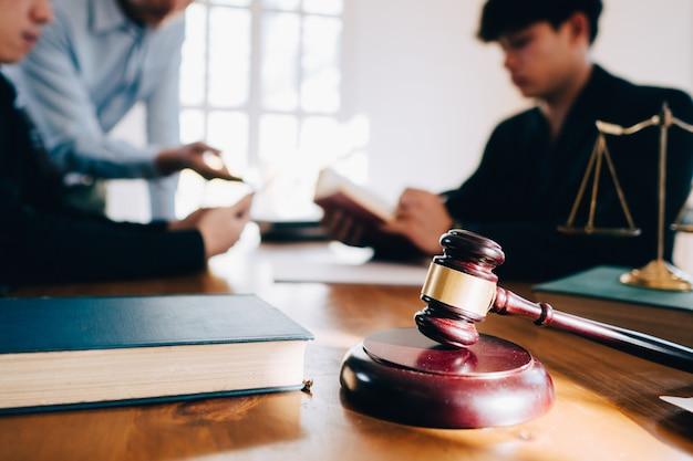 ビジネスの男性とチームと弁護士事務所の木製の机の上の真鍮製スケールと契約書を議論します。法律、法律サービス、助言、正義の概念。