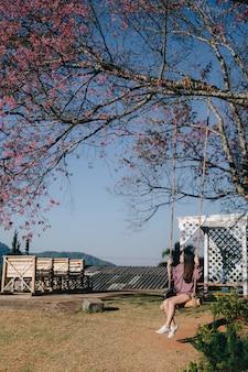ピンクのトランペットの木の花が付いている公園のブランコに乗って若い女性