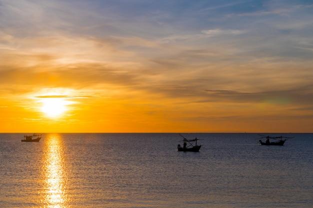 ビーチ、シルエットの漁船と朝の日の出の夏の間に海。