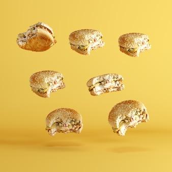 黄色の背景に浮かぶハンバーガー。ミニマ食品アイデアコンセプト。