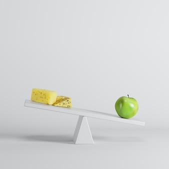 白い背景の反対側にチーズとシーソーを傾ける青リンゴ。