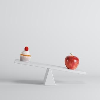 白い背景の反対側にカップケーキとシーソーを傾ける青リンゴ。