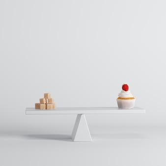 白い背景の反対側に砂糖とカップケーキアップルシーソー。