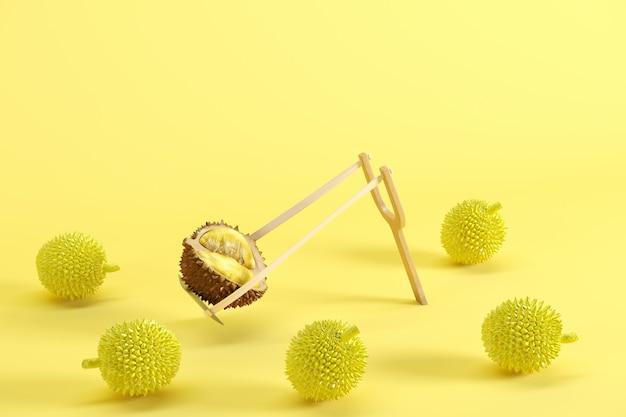 Выдающийся свежесрезанный спелый дуриан в рогатке на желтом фоне