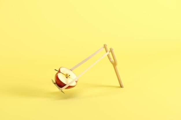 黄色の背景にパチンコの赤いリンゴの半分