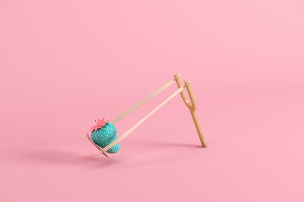 Клубника окрашена в синий цвет с розовыми листьями и стеблем в рогатке на розовом фоне