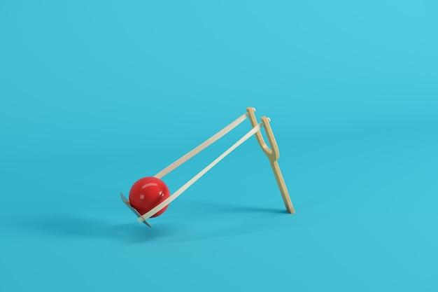 Красный шар в рогатке на синем фоне