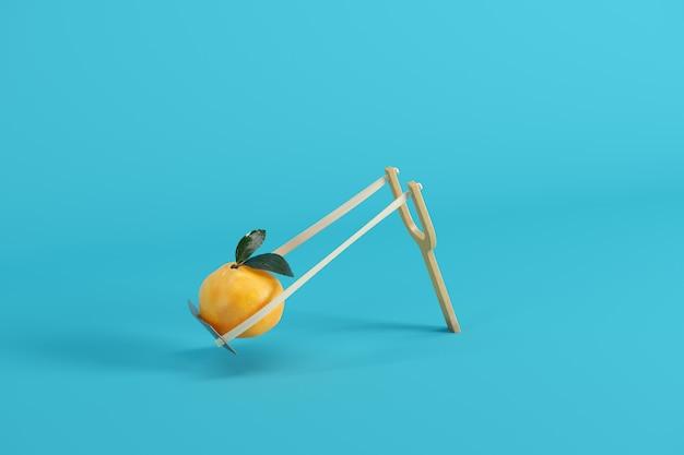 Апельсин в рогатке на синем фоне
