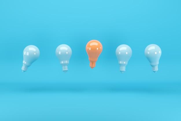 青に浮かぶ青い電球の中で傑出した明るいオレンジ色の電球