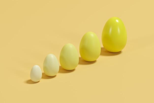 黄色の背景にさまざまなサイズの黄色の単調卵。最小限のイースターの考え。