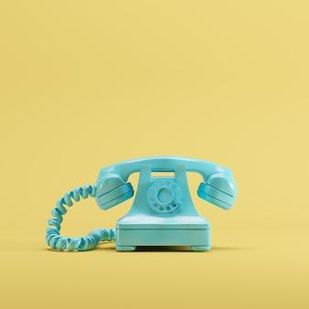 黄色のパステルカラーの背景に青いビンテージ電話。最小限のアイデアのコンセプトです。