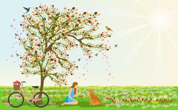 女性と犬は花の木の下に座っています