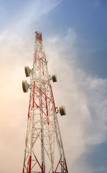 Телекоммуникационные полюсные башни телевизионные антенны с фоном голубого неба