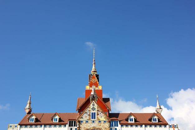 青い空の白い雲と美しいタイの屋根のスタイルを適用