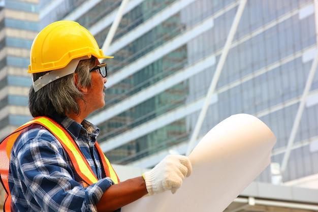 Работник в форме обеспечения безопасности план и глядя на строительную площадку