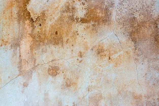 Старая, выветренная лепная стена, замусоренная коричневатыми пятнами и трещинами в качестве фона