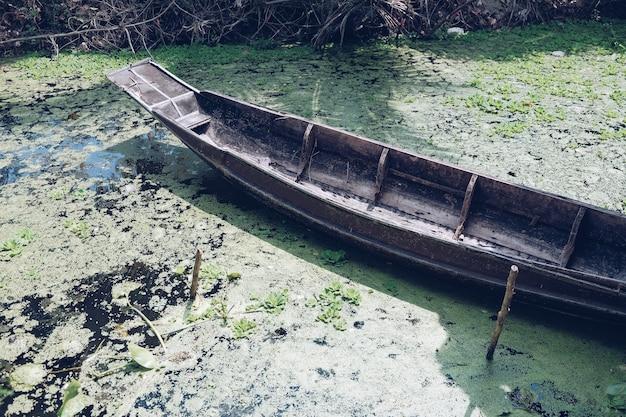 川でヴィンテージの木製ボート。川の土手近くに立っている木製のボート。