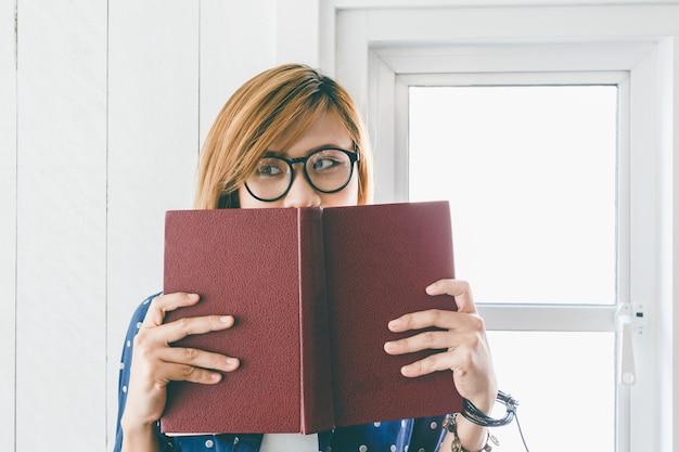 Молодая женщина, холдинг и чтение книги в окне в доме