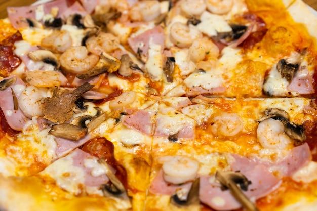 木製のテーブルでシーフードピザのクローズアップ。