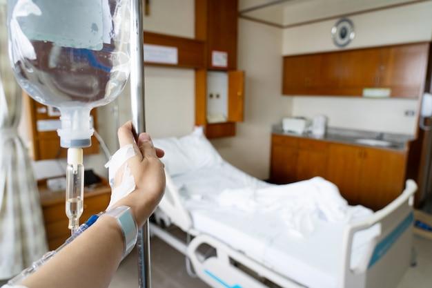手のビューは忍耐強いベッドの背景が付いている静脈内液体に掛かる。
