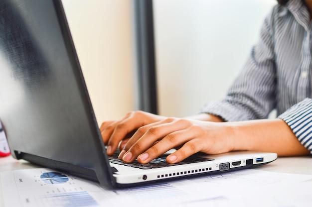 ラップトップで仕事をしているオフィスの退屈な若い女性とコンピュータの画面を凝視する