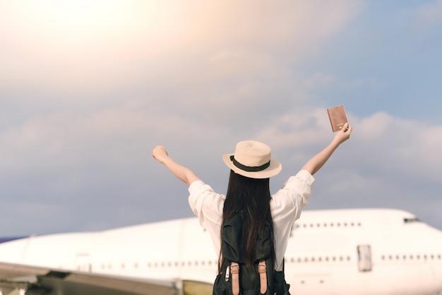 飛行機をキャッチするパスポートと空港で幸せな若い観光客。自由とアクティブなライフスタイルのコンセプト