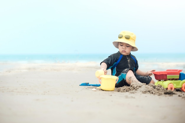 熱帯のビーチでビーチおもちゃで遊ぶかわいい男の子
