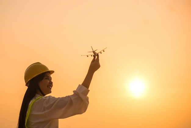 夕日と手で飛行機を保持している従業員女性の笑みを浮かべてください。