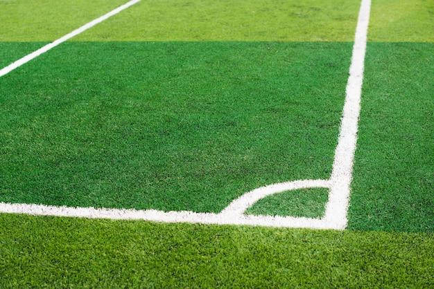 緑のサッカー場の白い線コーナー