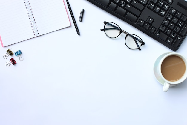 Ноутбук, ручка, клавиатура и кофейная кружка на белом столе.