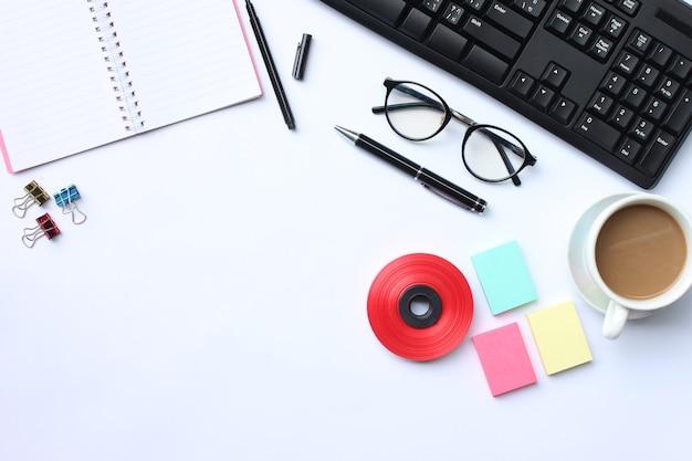 Ноутбук, ручка, клавиатура, кофейная кружка и аксессуары на белом столе.