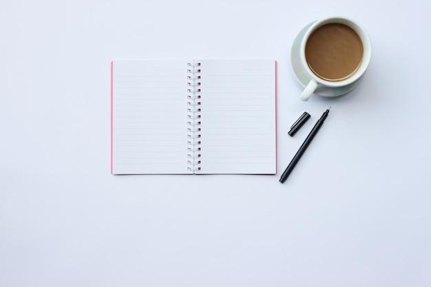 Ноутбук, ручка и кофейная кружка на белом столе.