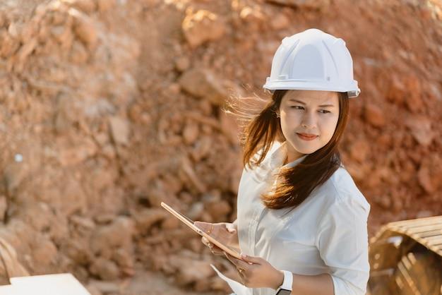 白い安全ヘルメットを持つアジア女性土木技師が工事現場を訪問します。