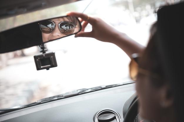 白いシャツのアジア女性は鏡をのぞいて、彼女の車に坐っている間笑顔