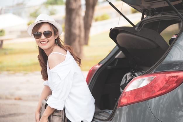ハッチバック車に座っている女性旅行者