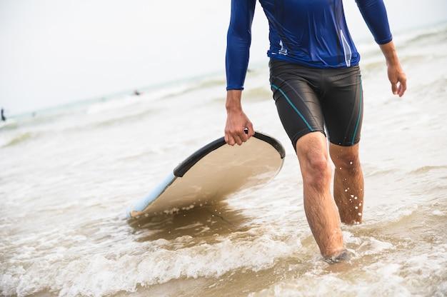 アジア人はビーチでサーフボードを運ぶ