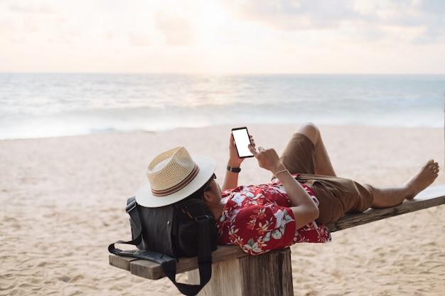 アジア人の男性がビーチでスマートフォンで横になっています。