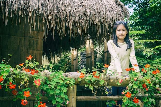 アーチ型の竹の上に立つ女の子の屋外の肖像公園、ヴィンテージスタイルのタイの伝統的な家