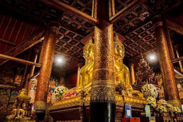 Большая золотая статуя будды посреди зала храма