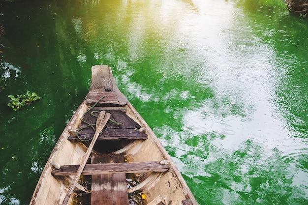 タイの田舎の有名な運河に氾濫している古い木製のボート