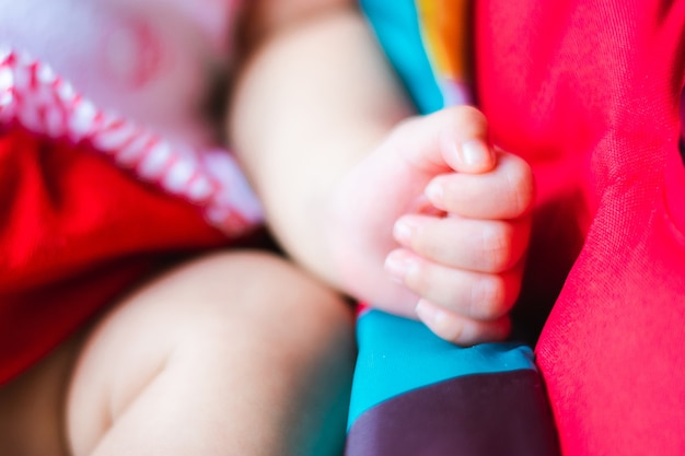 かわいいアジア人の赤ちゃんの小さな指がカーシートで眠っている