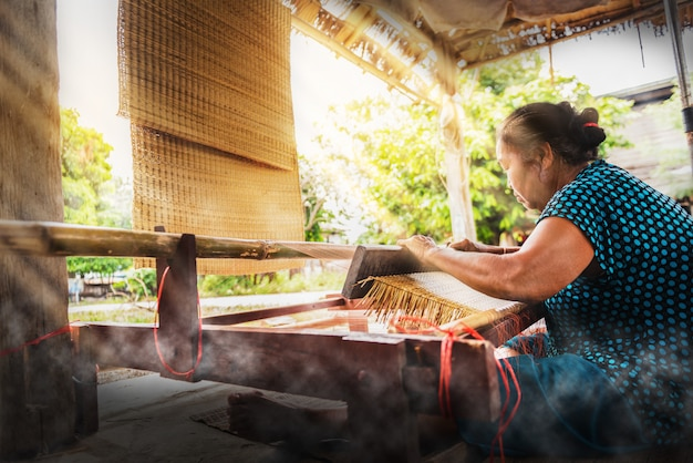 アジアの女性の乾いたパピルスから典型的なタイのわらのマットを織り