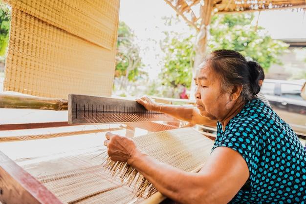 Азиатская женщина плетет типичную тайскую соломенную циновку из сухого папируса