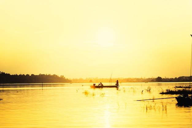 夕焼け空に対してマウンテンビューの湖で小型漁船のシルエット男