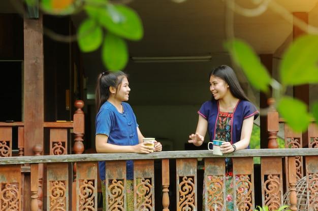 美しいアジアの女の子はタイの田舎での朝のコーヒーとの会話を楽しむ