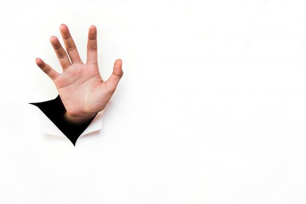 Рука, протягивающаяся от порванного листа белой бумаги
