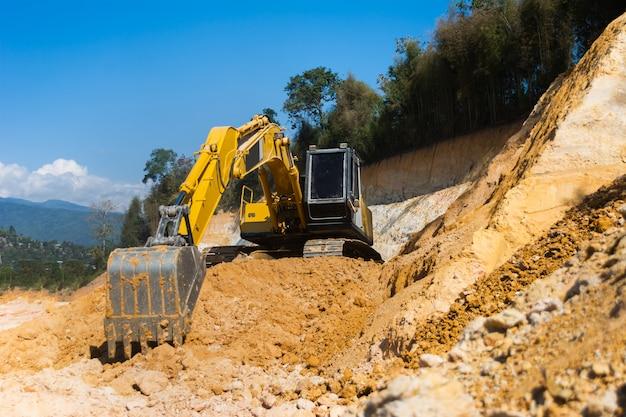 砂と土の土地をきれいにするために工事現場で働く産業掘削機