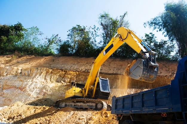砂と土の土地をきれいにするために工事現場で働く産業掘削機とトラック
