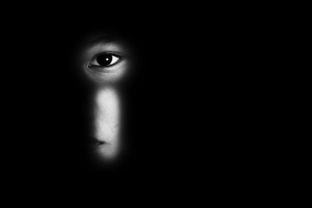 Глаз мальчика через ключевое целое, концепцию жестокого обращения с детьми