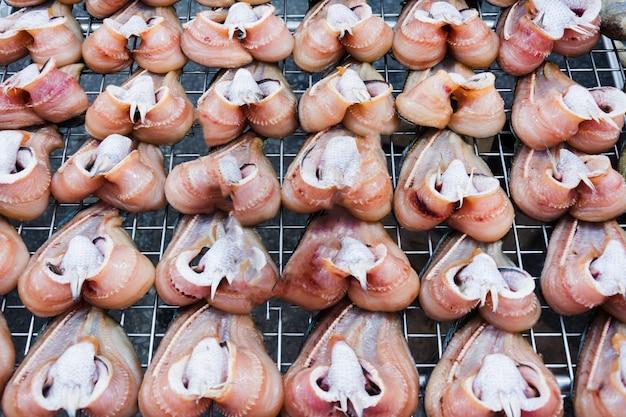 Продажа сухой полосатой рыбы змееголов на уличном рынке